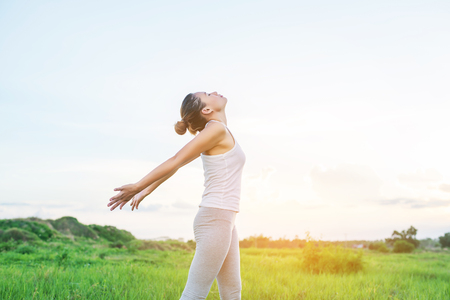Healthy woman : Young woman spreading hands with joy the sun at meadows. Stock Photo