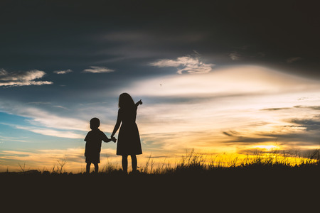 Silhouette of Mother encouraged her son outdoors at sunset, silhouette concept