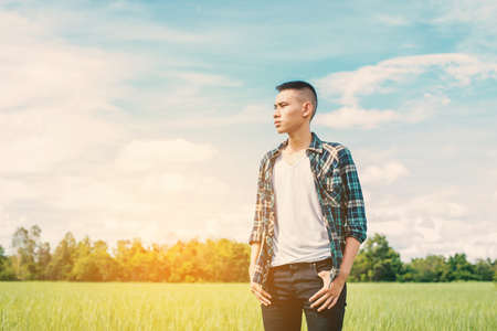 young handsome man standing in green field.