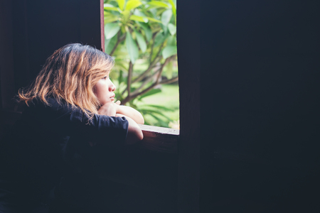 Frauen-Lifestyle-Konzept: Junge traurige Frau auf der Bank neben Fenster Blick nach außen, Trauer, Einsamkeit sitzen.