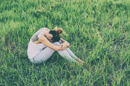 self worth: Woman life concept: sad woman hug her knee and cry in meadows.