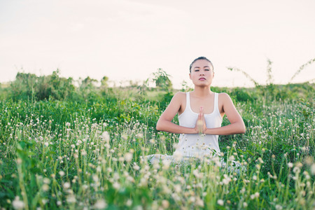 joined hands: healthy and beautiful young yoga  woman sitting with joined hands at meadows. Stock Photo