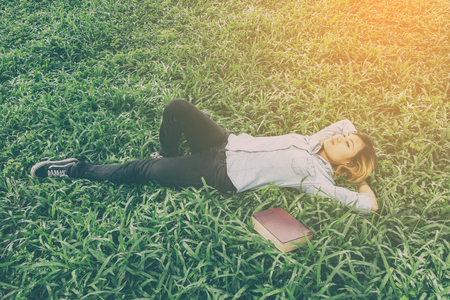 Young hipster woman lying down on grass when she tired after read book.