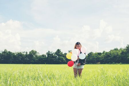 Happy young beautiful woman and colorful balloons in grassland.