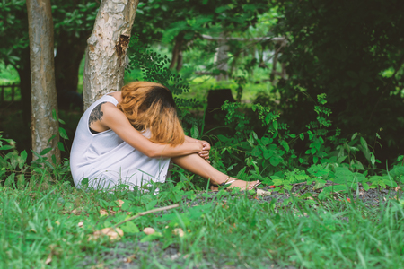 hugging legs: young hipster woman, sad, long-haired  sitting hugging legs.