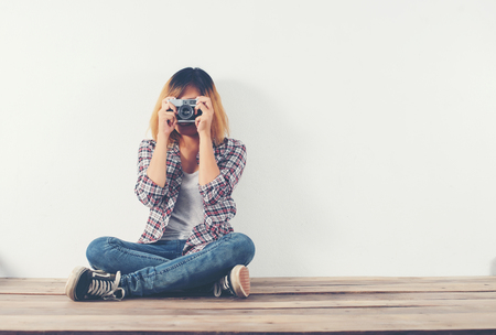Young hipster photographer woman taking photo and look at camera sitting on wooden floor.