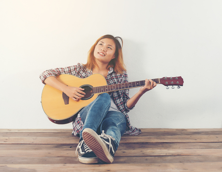 Hipster woman style portrait chillin? with guitar look so happy. Imagens - 77500354