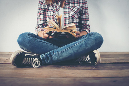 Close-up of hipster woman hands holding open book sitting on wooden floor. Imagens