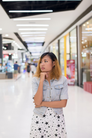 Young beautiful woman standing thinking something at shopping mall.