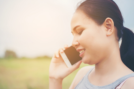 Young beautiful woman using smartphone and smiling in the park. Imagens - 77500362