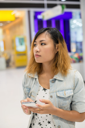 young beautiful woman wearing jean jacket texting on the smartphone walking in the shopping mall. Imagens - 77500364