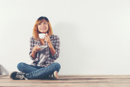 Happy woman sitting on wooden with coffee mug isolated on white.