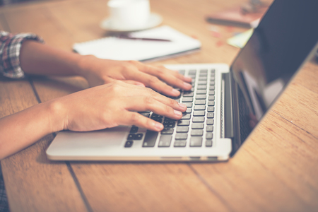ady: Close-up woman hands typing on laptop in office. Stock Photo