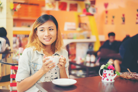 Portrait of young beautiful woman sitting in a cafe  holding hot coffee.