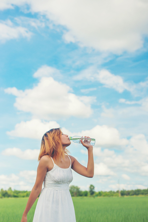Women lifestyle concept: young beautiful woman with white dress drinking water at summer green park. Imagens - 77500367