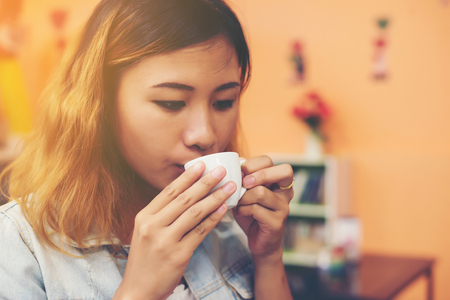 Portrait of young beautiful woman sitting in a cafe  drinking hot green tea. Imagens