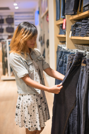 Happy young woman looking at clothes sale in the shop. Imagens - 77500371