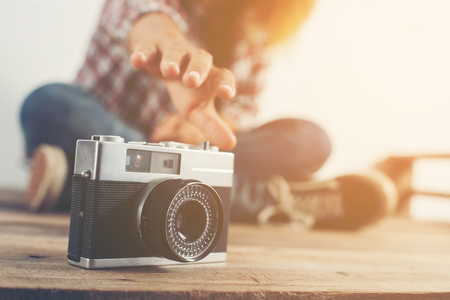 Young hipster woman hand reach out for catch retro camera.