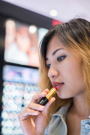 Beautiful young woman select color lipstick to buying at shopping mall.