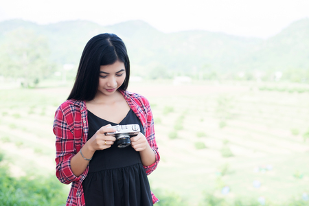 Young hipster woman photographer holding a vintage camera. Imagens - 77500379