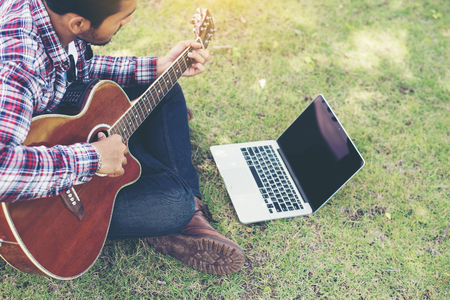 Young hipster man practiced guitar with laptop in the park,happy and enjoy playing guitar. Imagens - 77500380
