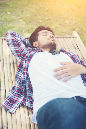Happy young hipster lying on bench in the nature park. Imagens - 77500395
