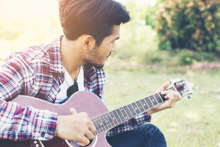 Young hipster man practiced guitar in the park,happy and enjoy playing guitar. Stock Photo