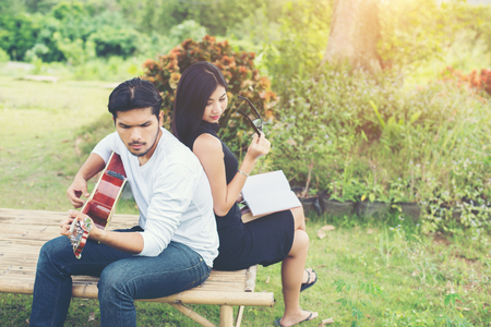 Young charming couple in love playing acoustic guitar in the park.Relaxing with nature,lifestyle concept.