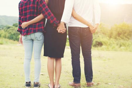 Triângulo do amor, o homem está abraçando uma mulher e ele está de mãos dadas com outra garota, parada ao ar livre no parque.