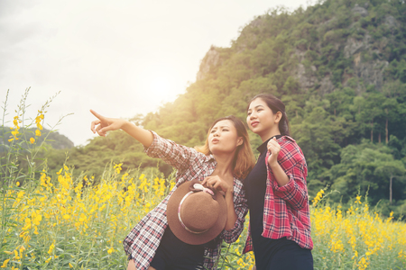 Two hipster women traveling and pointing hands enjoying with flower field together, relaxing good time sunny day.