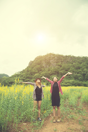 Two hipster woman traveling and raising hands enjoying with flower field together, relaxing good time sunny day. Stock Photo