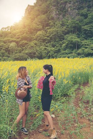 Two hipster woman traveling and enjoying with flower field together, relaxing good time sunny day.