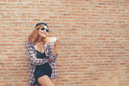 Cheerful woman in the street drinking morning coffee against brick wall.