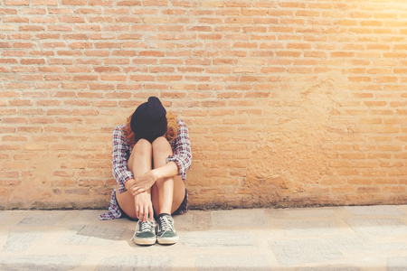 Young woman sad sitting against brick wall alone.