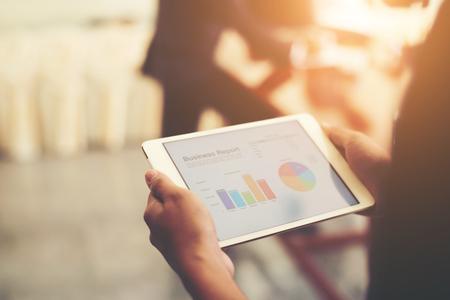 main d & # 39 ; affaires main tenant des statistiques financières affichées sur l & # 39 ; écran de la tablette au bureau