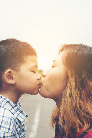 Little boy kissing his mom with the natural roadside. Stock Photo