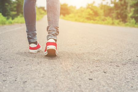 Woman feet with red sneaker shoes walking on the roadside.