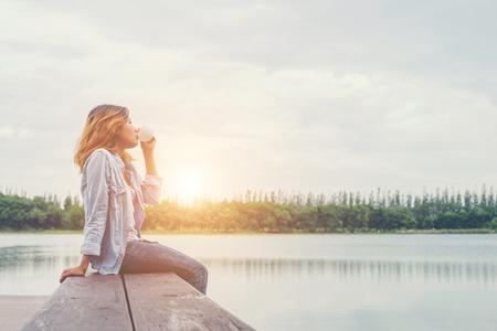 新鮮な空気と朝日の出とリラックスの湖の上に座ってコーヒー カップを保持している若い美しいヒップ女性。