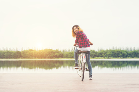Woman feet pedal bike on the wooden bridge looking back at camera,Relaxing freedom,ready to go riding. Stock Photo