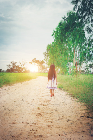 pass away: Little girl with long hair wearing dress is walking away from you down rural road.