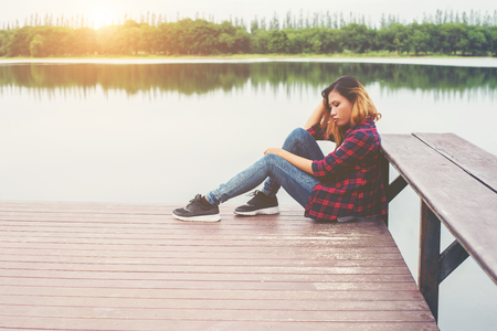 Sad hipster woman sitting on the pier with sadness.