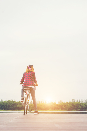 Back of young hipster woman cycling with bicycle on a pier,Relaxing enjoy summer holiday.
