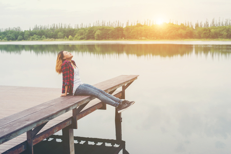 Young hipster woman sitting on wooden pier, Relaxing lying leg down to the lake.