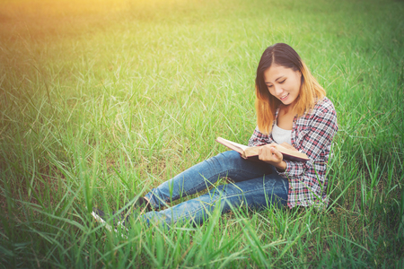 Young beautiful hipster sitting reading book on the grassland. 版權商用圖片