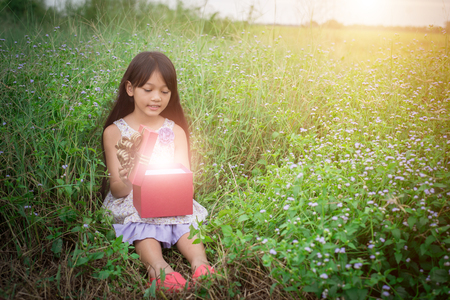 little girl sitting by the field with a gift and looking at it, So surprised! Stock Photo