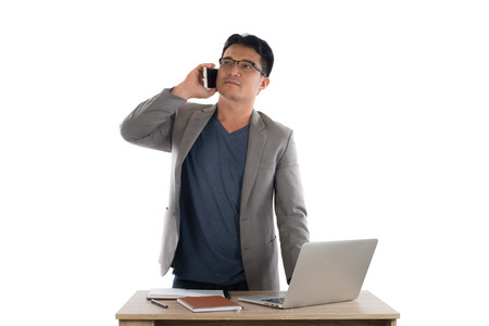 Businessman working on laptop and calling on phone, white background.