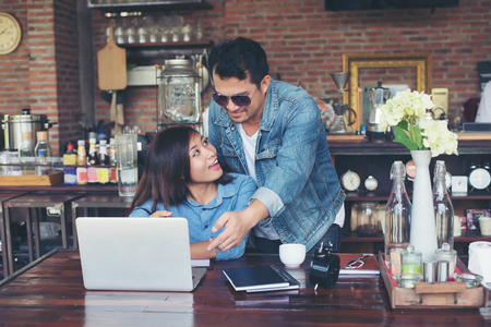Two young business working on their laptop, While sitting in a cafe, Talking serious with work. Business life concept. Imagens - 77500918
