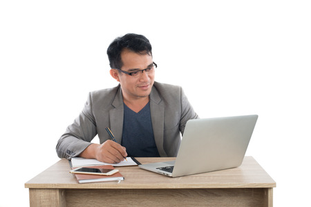 businessman writing notes on a writing pad while sitting at his desk behind his new notebook isolated on white background. Imagens - 77500932