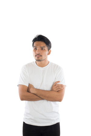 Young handsome man with t-shirt standing arms crossed on isolated white background . Imagens