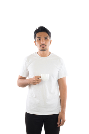Portrait of young man holding a cup of coffee isolated on white background.